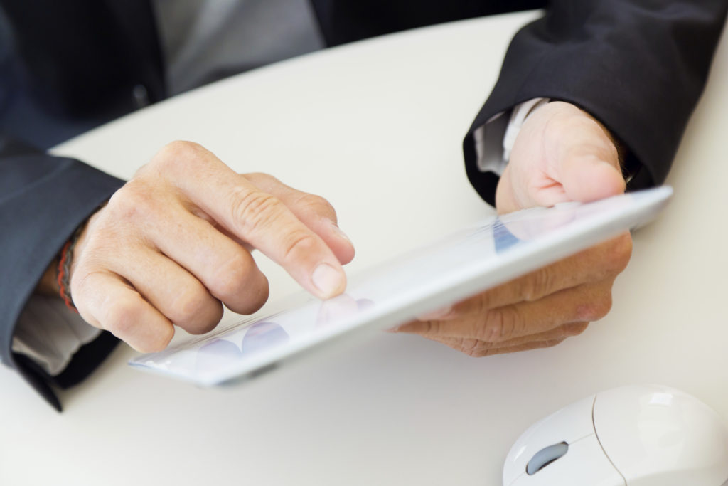 Businessman finger pointing to the screen of a digital tablet.