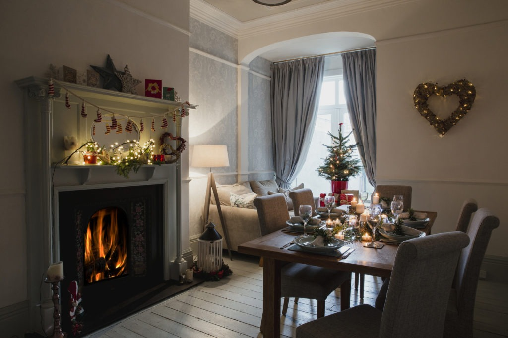 Dining room of a home decorated for Christmas. The table is set ready for Christmas dinner and the fire and candles are lit.