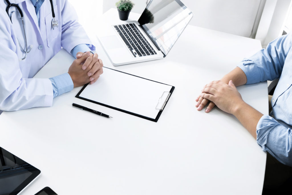 close up of patient and consultant doctor give an advice in a hospital or clinic